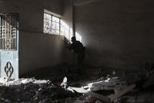 A Free Syrian Army fighter takes up position as he sneaks a look out of a window in Deir al-Zor