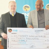 FNB CEO Emil Heppell (left) hands over the cheque to His Majesty King Letsie III at the Royal Palace on Tuesday.