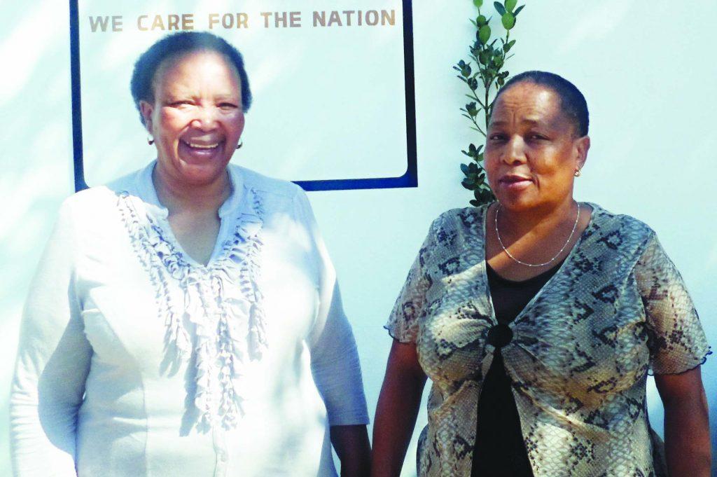 Care for Basotho National Coordinator Mathasi Kurubally  (left) stands with President Malintle Matlakeng outside the new Care for Basotho premises 1
