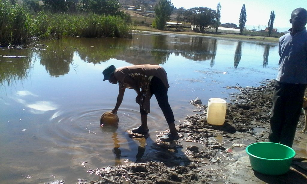 Hlotse woman draws water from the dam