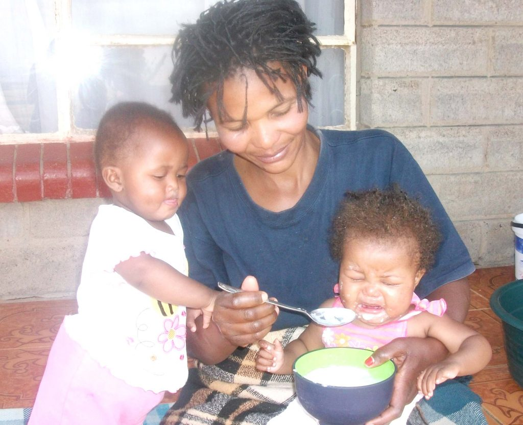 'Mantsoaki Rakotsi feeds baby Blessing while her twin sister apears to wonder what could be going on