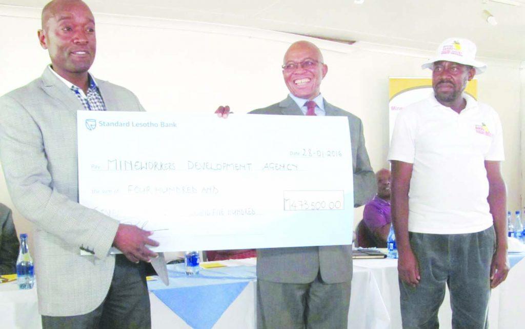 Harmony's Lebohang Shabe (left) hands over the cheque to BAHOFA represenattives