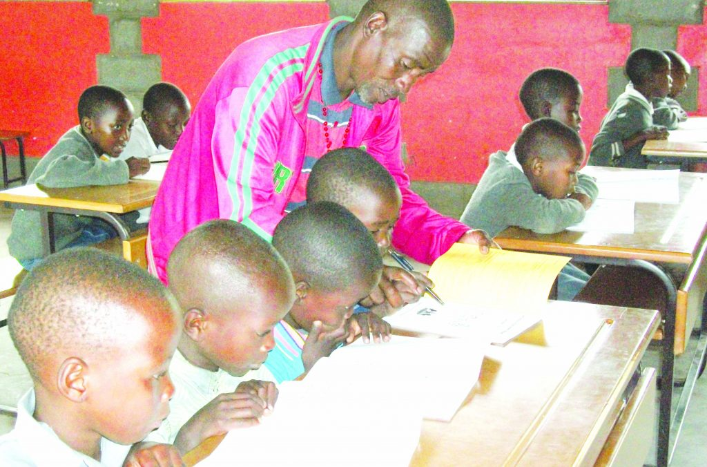 The only teacher at Ntamaha Primary School, Mr Matsa Monaheng assists one of the class one pupils while the other classes concentrate on their own work