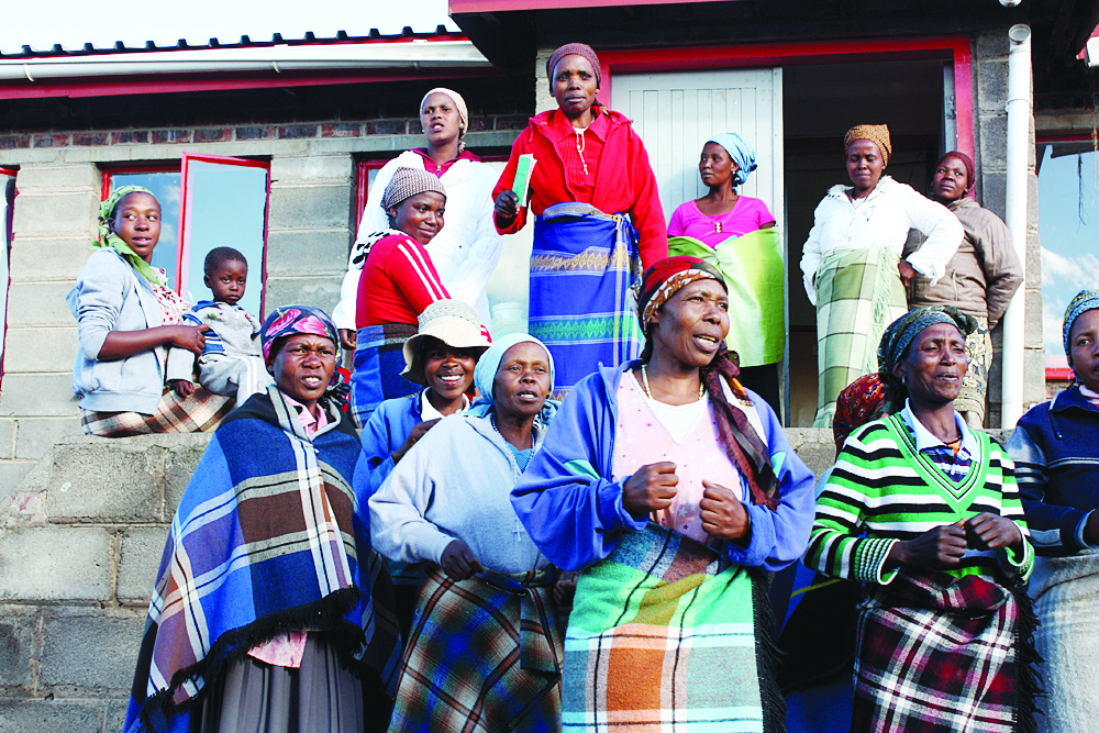 """A group of women sing outside the Bobete Health Clinic in Lesotho. Lesotho has one of the highest rates of both HIV infection and maternal mortality  in the world. """"This clinic was where we piloted the Maternal Mortality Reduction Program in Lesotho. Some of the women in the photo are Community Health Workers (who are trained to educate and accompany people in their villages to the clinic for health services, and receive performance-based pay for their work), and some are expectant mothers who have come to the clinic for care,"""" says Riley. Jennie Riley, is a Concord High School graduate working in Lesotho with the aid group Partners in Health.  courtesy photo"""